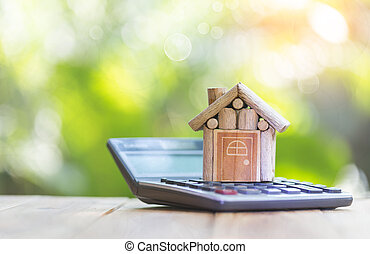 House is placed on the calculator. planning savings money of coins to buy a home concept for property,