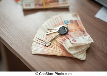 House key with trinket house shaped against the background of Russian money. Rental estate. Sale property template.