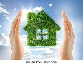 House made of grass between hands