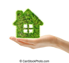 House made of grass on female hand
