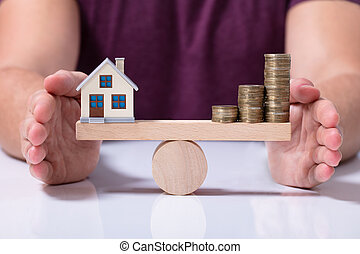 House Model And Money Coins Balancing On A Seesaw