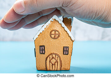house model covered by a hand concept of home insurance and safety