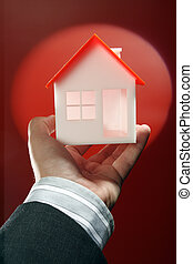 Real property or insurance concept - House model in hand. ...
