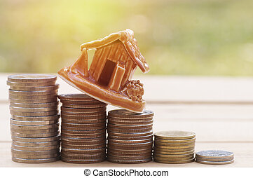 house model on money coins, savings plans for housing ,green background, financial concept