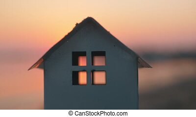 House model on the beach at sunset - Close-up shot of house...