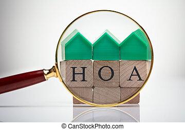 House Model Over Wooden Blocks Seen Through Magnifying Glass
