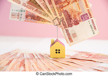 house model set on banknote for concept investment mortgage fund finance and home loan. Small wooden house on the background of russian banknotes. Symbolic image of buying or renting a house.
