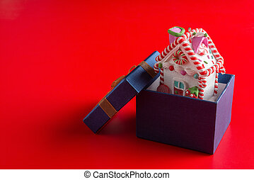 house model with Christmas decoration inside a present box on red background