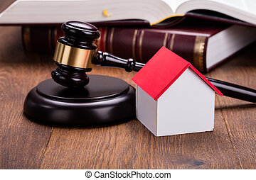 House Model With Gavel On Wooden Table