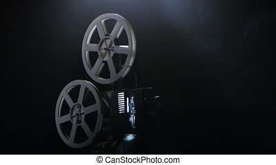 Working projector side view, smoke on black background, moving the reel is wound on the film with one another, lamp lights inside the mechanism, of the lens are projection rays