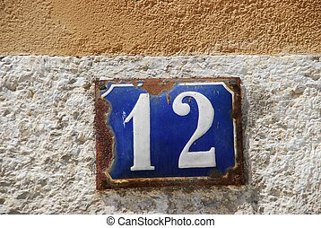blue and white rusty metallic number (12) hanging on stone wall