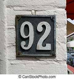House number 92 - House number ninety two on a white wall