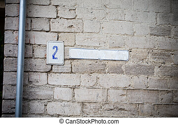 House number plate on a brick wall.