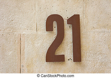 House number tewnty one attached to a stone wall.