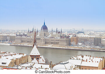 house of parliament over snowed roofs of Buda hill at winter day, Budapest, Hungary