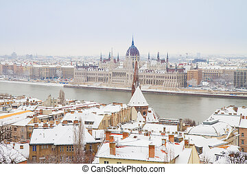 house of parliament over snowed roofs of Buda hill, Budapest, Hungary