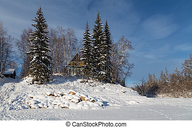 House on shore of the river in wintertime