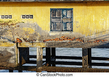 house on stilts in the open sea. a window frame with old paint cracked.