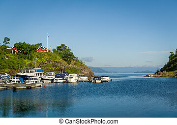 House on the hill and small motor boats docked at pier.