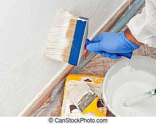 House painter at work painting a wall with a brush