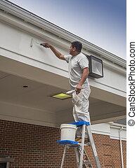 House painter - Hispanic male painting building soffit