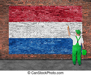 House painter paints flag of Hetherlands on brick wall -...