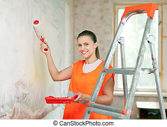 house painter paints wall - Female house painter paints wall...