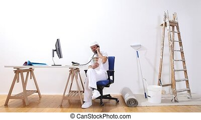 house painter with a computer talk on the phone, looks at...