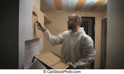 house painter with glasses and beard roller paints the wall.