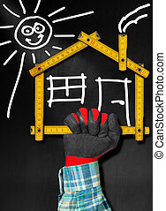 Hand holding a wooden meter ruler in the shape of house with sun, door, window and smoke from the chimney. On a blackboard. Concept of house project