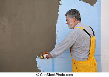 House renovation, polystyrene wall insulation - Worker...