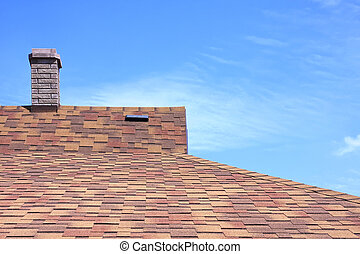 House roof covered with a bitumen tile against the summer dark blue sky