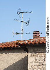 House roof with old type antennas - Segment of house wall...