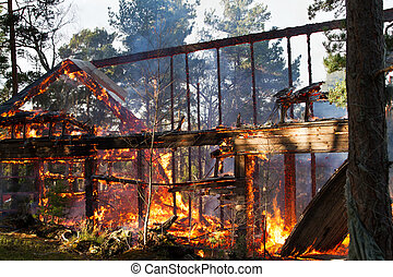 House ruin after fire, visible flames and glow