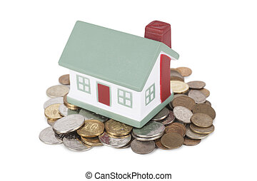 House sale - Little house toy on a heap of coins isolated...