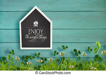 House shaped chalkboard and grass on wooden background