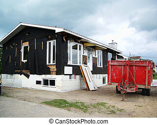 Home renovations: old house with siding removed on new styrofoam foundations