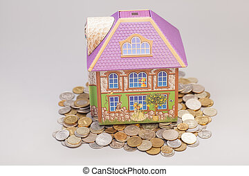 House standing on heap of coins on gray. Real estate concept