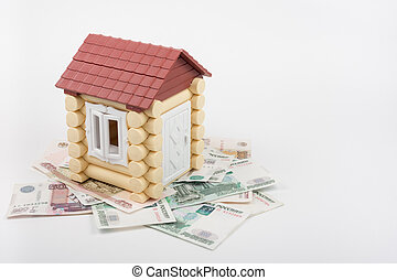 House stands on the banknotes of Russian rubles, from the roof sticking out of ten US dollars banknote