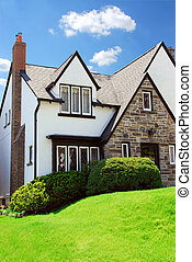 House - Residential tudor style house with blue sky in...