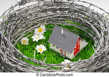 House surrounded by barbed wire - A house on a green field...