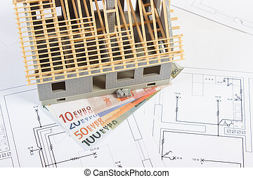 House under construction and currencies euro on electrical drawings, concept of building home
