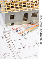 House under construction and currencies euro with electrical diagrams for project, building home cost concept
