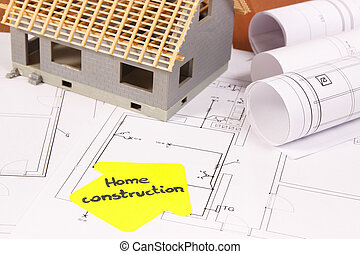 House under construction and rolls of electrical diagrams or blueprints, building home concept