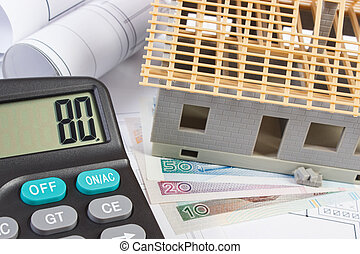 House under construction, calculator and polish currency on electrical drawings, concept of building home