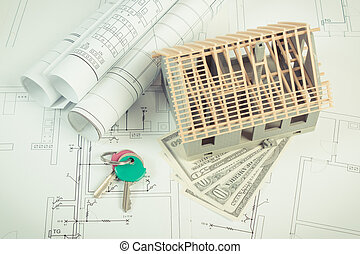 House under construction, currencies dollar and keys on electrical diagrams for project, building home cost concept