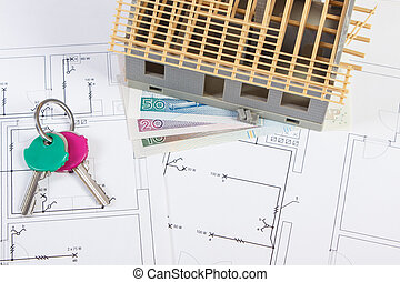 House under construction, keys and polish currency on electrical drawings, concept of building home