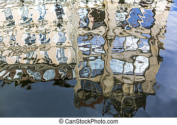 house with blue sky mirroring in a vibrant water surface