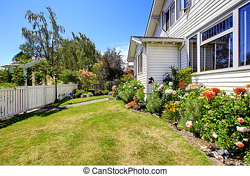 House with front yard landscape and white fence