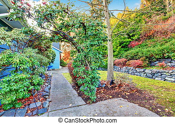 Backyard view. Summer garden with green archway and walkway